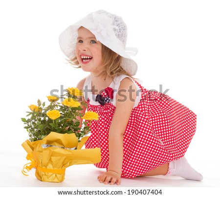 Cheerful little girl in panama and red dress with a bouquet of yellow roses - stock photo