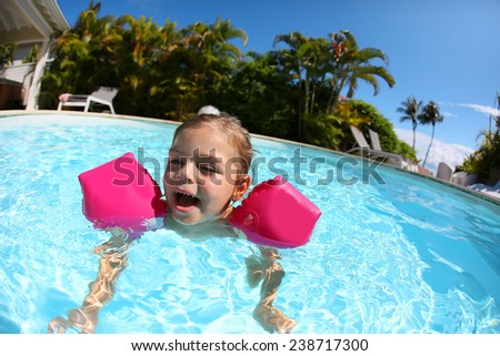 Cheerful little girl in swimming-pool - stock photo
