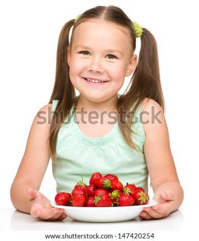 Cheerful little girl is eating strawberries, isolated over white - stock photo