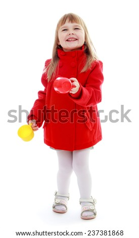 Cheerful little girl is holding a plastic cup. Happy childhood, fashion, autumnal mood concept. Isolated on white background - stock photo