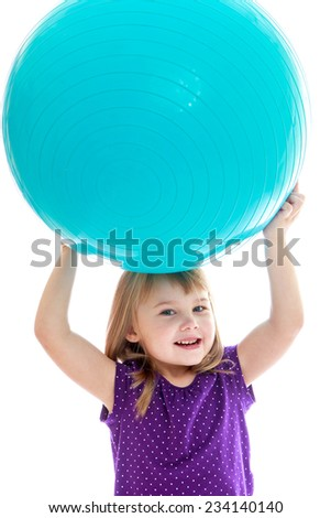 Cheerful little girl is holding her head on a large sports ball. Happy childhood, fashion, autumnal mood concept. Isolated on white background - stock photo