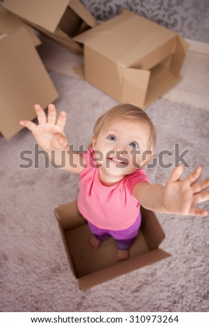 Cheerful little girl is standing in cardboard box with joy. She is raising her hands up with efforts and smiling. Her family is preparing to move in new building - stock photo