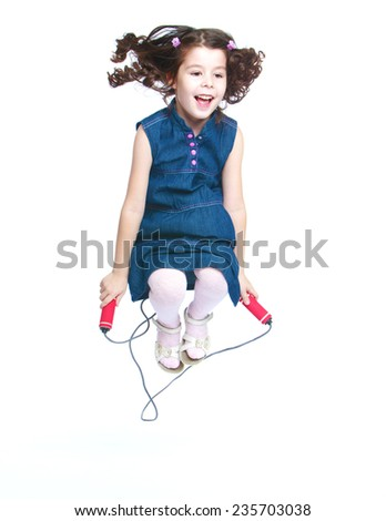 Cheerful little girl jumping rope.White background, isolated photo. - stock photo