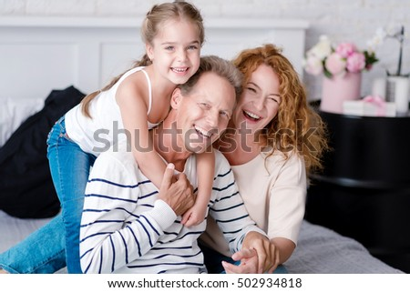 Cheerful little girl laughing with her grandparents