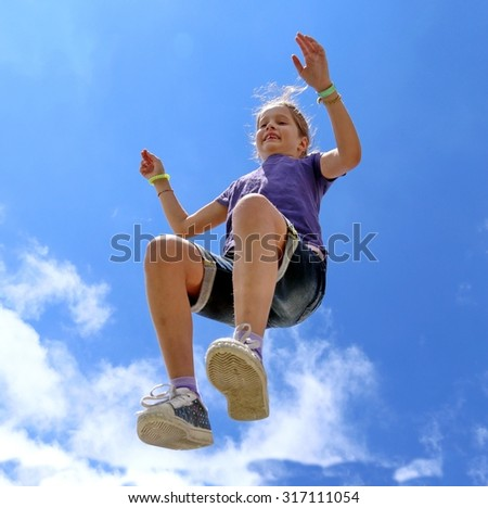 cheerful little girl makes a big jump and blue sky in summer
