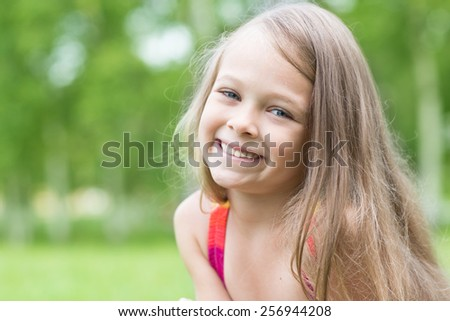 Cheerful little girl on a background of greenery in the park. Girl seven years. - stock photo