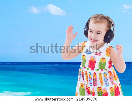 cheerful little girl on the beach listening to music in big black headphones. - stock photo