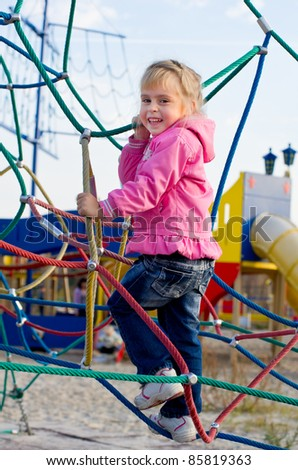 Cheerful little girl on the playground. Active holidays - stock photo