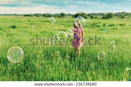 Cheerful little girl playing among soap bubbles on green meadow in summer. Focus on soap bubbles in foreground - stock photo