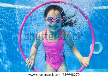 Cheerful little girl playing under  water in pool. - stock photo
