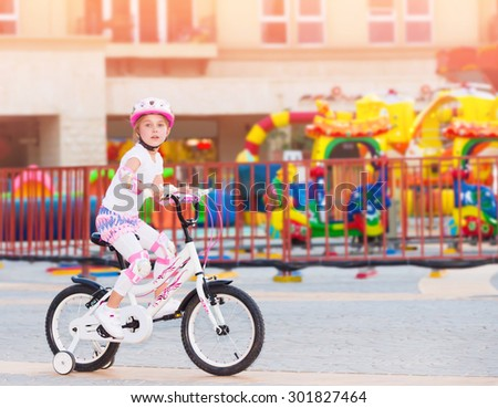 Cheerful little girl riding on the bicycle in amusement park, happy carefree childhood, having fun outdoors in summer camp  - stock photo