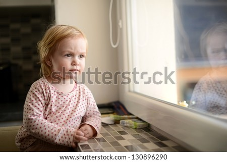 cheerful little girl sits at window portrait