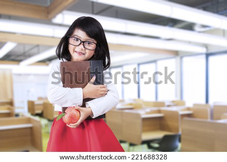 Cheerful little girl standing in class while holding a book and apple - stock photo
