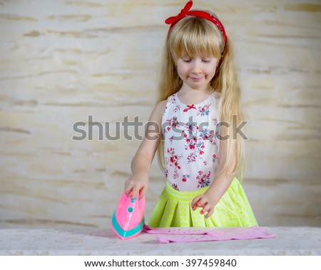 Cheerful little girl using toy iron on her pink clothing over stone table with yellow water spritzer next to it