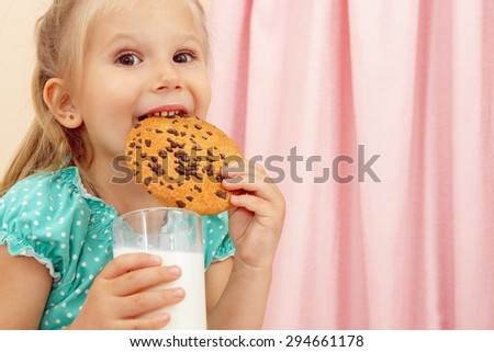 Cheerful little girl with chocolate chip cookies and milk - stock photo