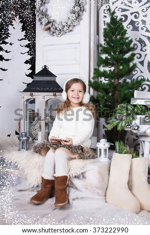 Cheerful little girl with ear muffs on her head sitting near green tree