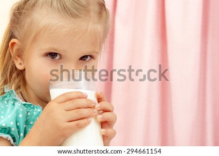 Cheerful little girl with glass of milk - stock photo