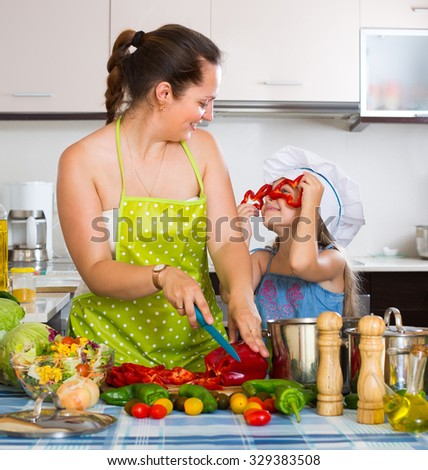 Cheerful little girl with mom cooking vegetable soup at home kitchen