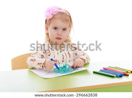 Cheerful little girl with short blond hair who is holding a pink headband in a bright silk shirt sitting at the table and drawing on a white sheet of blue felt-tip pen, lie near a lot of colored - stock photo