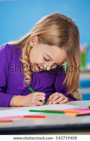Cheerful little girl with sketch pen drawing in kindergarten - stock photo
