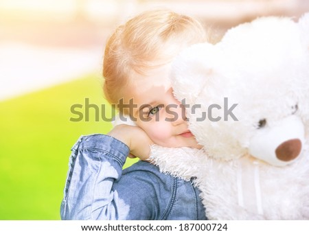 Cheerful little girl with soft bear toy playing outdoors, having fun on backyard in sunny day, summer holidays, happy childhood concept  - stock photo