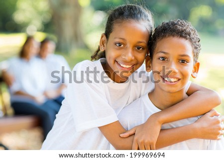 cheerful little indian sister and brother standing in front of parents in the park - stock photo