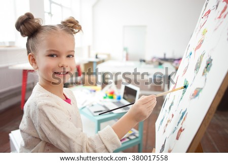 Cheerful little kid is painting with joy - stock photo