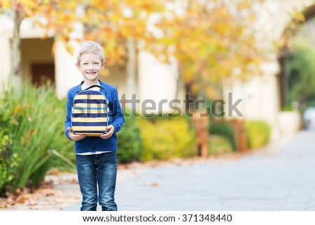 cheerful little schoolboy holding lunchbag, back to school concept - stock photo