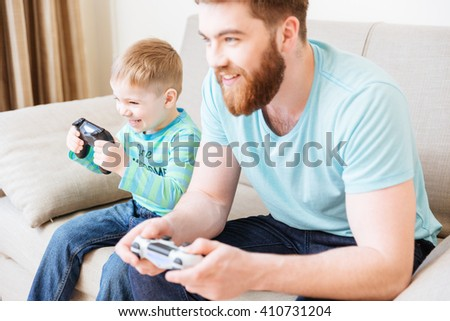 Cheerful little son and dad playing computer games at home together and smiling