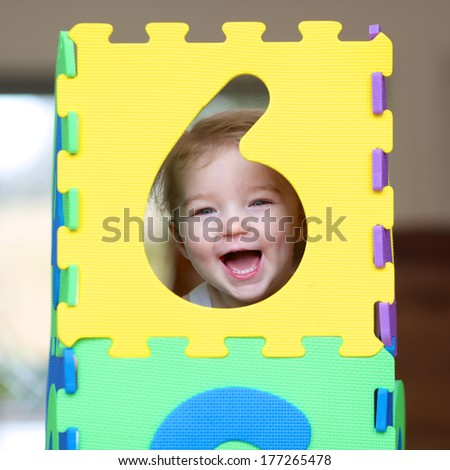 Cheerful little toddler girl playing hide and seek with colorful numbers puzzles - stock photo