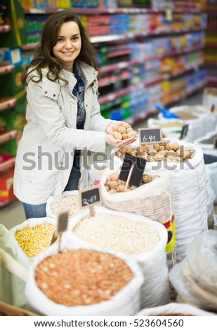 Cheerful long-haired spanish woman purchasing lentil in shop