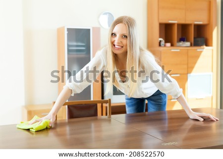 Cheerful long-haired woman cleaning table at home - stock photo