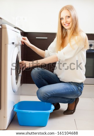 Cheerful long-haired woman doing laundry at her home - stock photo