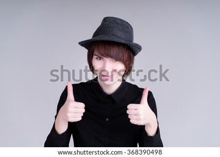 Cheerful lovely girl in the hat and black shirt showing thumbs up over gray background. Looking at camera. Isolated on grey background. - stock photo