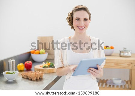 Cheerful lovely woman holding her tablet standing in her kitchen at home - stock photo