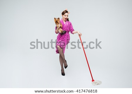 Cheerful lovely young housewife with dog cleaning the floor - stock photo