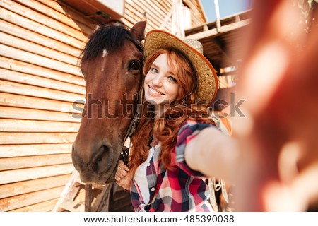 Cheerful lovely young woman cowgirl standing taking selfie with her horse on farm