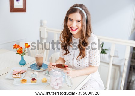 Cheerful lovely young woman eating dessert in cafe and smiling - stock photo