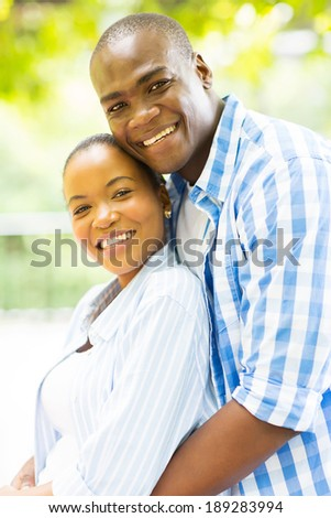 cheerful loving african couple hugging