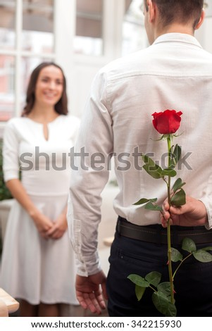 Cheerful loving couple is dating in restaurant. The man is standing and holding a red rose behind his back. The woman is looking at him with love and smiling - stock photo