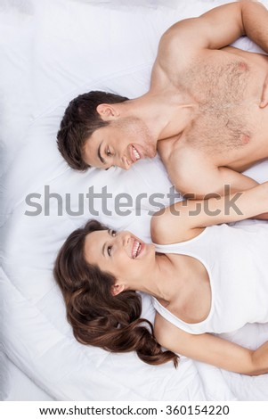 Cheerful loving couple is relaxing in bedroom