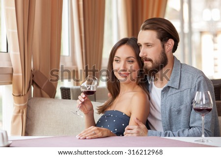 Cheerful loving couple is sitting and drinking red wine in restaurant. They are embracing and smiling. The couple is dreaming about their future. There is a gold ring on female finger - stock photo