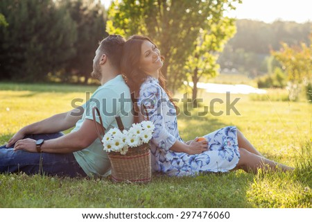 Cheerful loving couple is sitting on green grass and relaxing. The woman is leaning her back on her boyfriends one. She is smiling with happiness. There is basket with flowers between them - stock photo