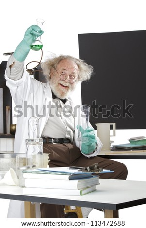 Cheerful mad senior scientist in lab measures green liquid in beaker. Frizzy grey hair, round glasses, lab coat, geek trousers, aqua rubber gloves, blank blackboard, vertical, high key, copy space.