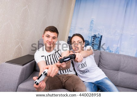 Cheerful male and female gamers are so passionated about the process of a game that even simulating the game steering movements holding  consoles in front of them sitting on the sofa at home - stock photo