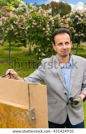 Cheerful male artist working  on a trestle and easel painting with oils and acrylics during an art class - stock photo