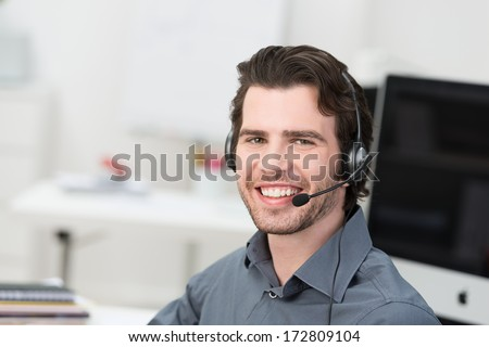 Cheerful male call centre operator or businessman wearing a headset sitting in an office grinning happily at the camera - stock photo