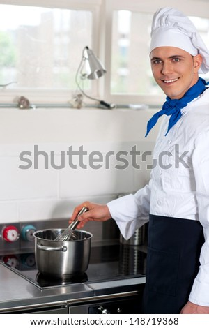 Cheerful male chef cooking in the hotel kitchen