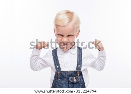 Cheerful male child is standing and preparing his fists for fighting. He is looking forward with aggression. Isolated and copy space in right side - stock photo