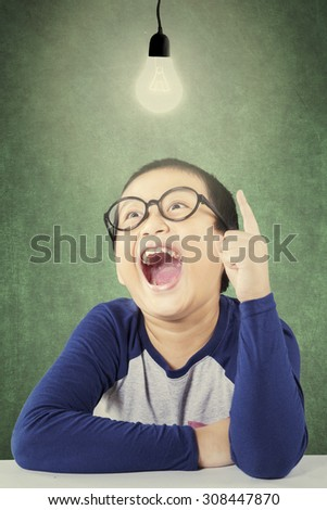 Cheerful male elementary school student get idea while pointing at a bright light bulb in the classroom - stock photo